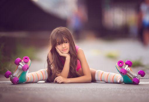Милая девочка сидит на асфальте на роликах
