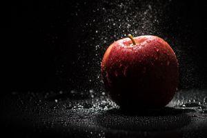 Яблоко и капли воды на черном фоне · бесплатное фото