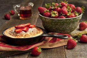 Свежеиспеченный пирог и миска с клубникой · бесплатное фото