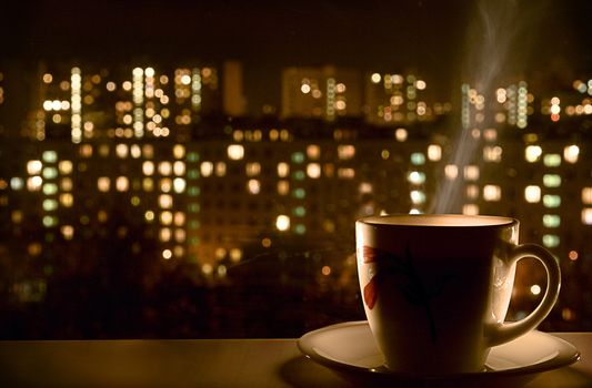 Coffee on the background of the city at night · free photo