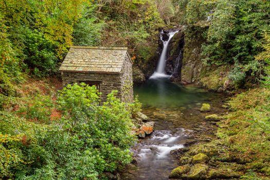 Избушка у водопада в лесу