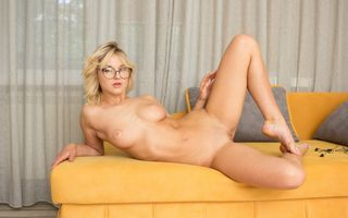 Голая блондиночка на диване в очках
