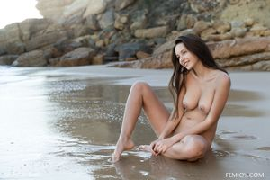 Naked Alice sitting on the shore of the beach