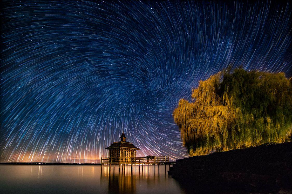Фото бесплатно Звездный вихрь в, Chez-le-Bartа, Швейцария, ночь, море, свечение, мостик, сияние, дерево, причал, пейзаж, пейзажи