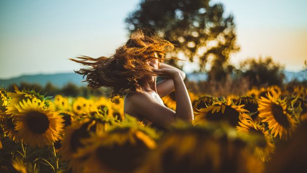 Girl with flying hair in sunflowers