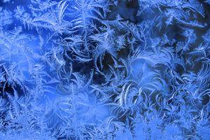 Рисует узоры мороз на оконном стекле · бесплатное фото