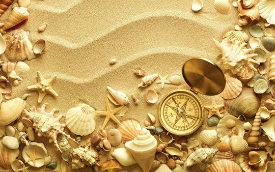 Компас и ракушки на песке