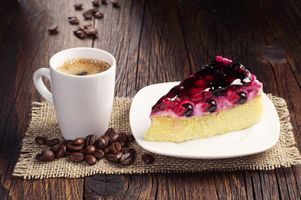 A piece of berry cake and cup of coffee · free photo