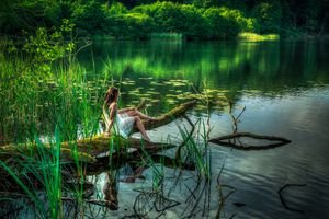 Одинокая девушка на берегу реки
