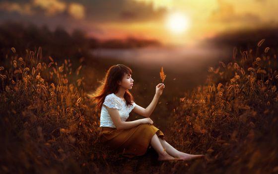 Китаянка с цветком на фоне заката солнца · бесплатное фото