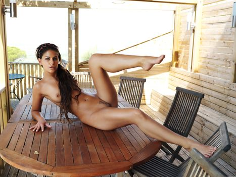 Tanned brown-haired woman on a wooden table