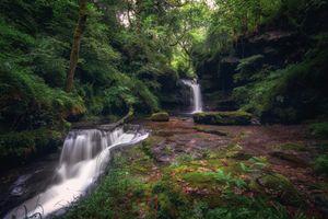 Ручей в лесу текущий по скале