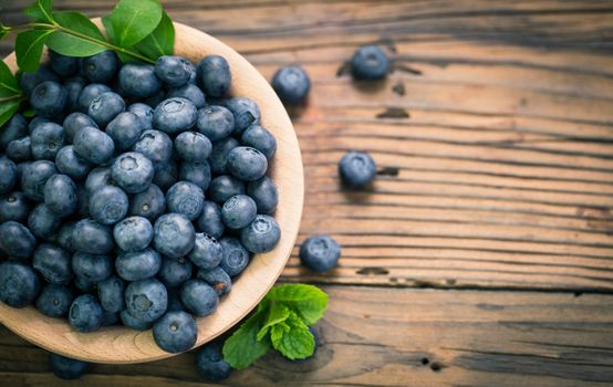 Blueberries in a bowl on a wooden table · free photo