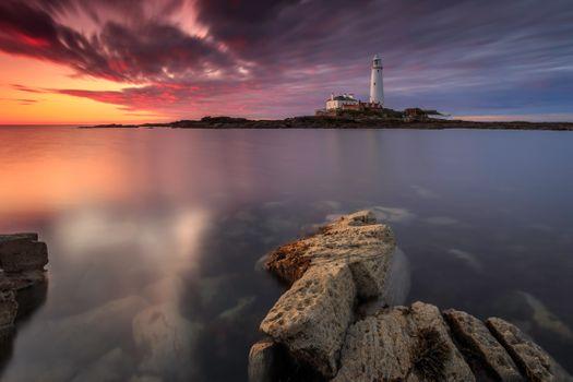 Вид на маяк с каменистого берега · бесплатное фото