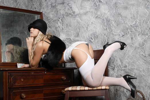 Girl in stockings poses at the mirror