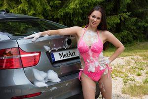 Девушка в купальнике моет машину, измазалась в пене